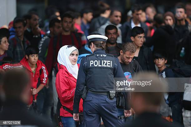 A young Muslim woman speaks to a policewoman as migrants who had arrived on a train from Hungary transfer to a chartered commuter train at Munich...