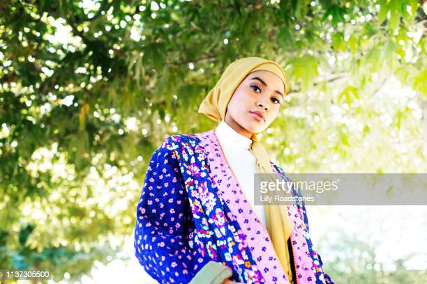 young muslim woman standing under trees - religion stock pictures, royalty-free photos & images