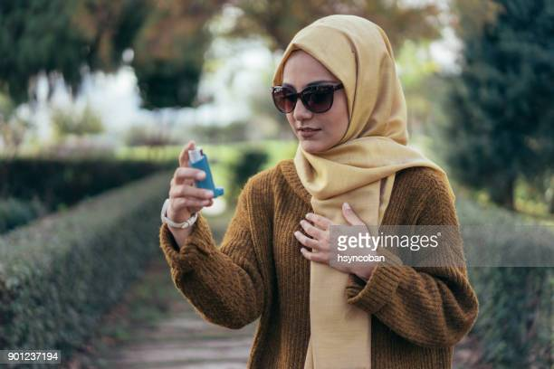 young muslim woman using an asthma inhaler outdoors - asthmatic stock photos and pictures