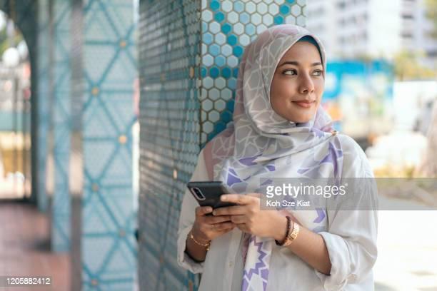 屋外で彼女の携帯電話を使用して若いイスラム教徒の女性 - シンガポール文化 ストックフォトと画像