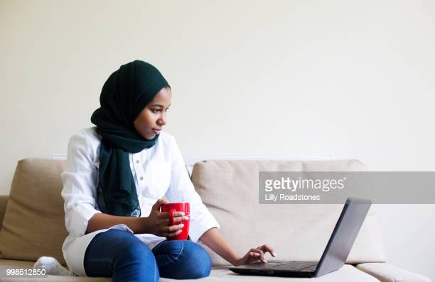 Young muslim woman using laptop and drinking hot drink
