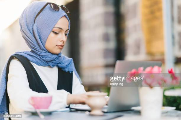 young muslim woman using laptop in street cafe - middle eastern culture stock pictures, royalty-free photos & images