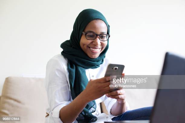 Young muslim woman using mobile phone and laptop