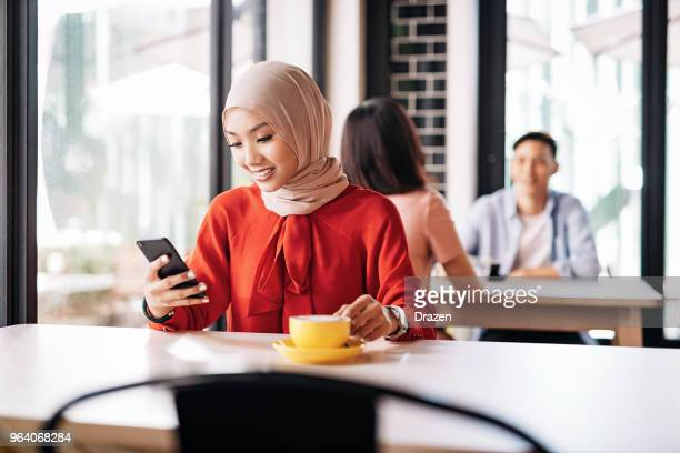 Young Muslim woman using phone for online shopping