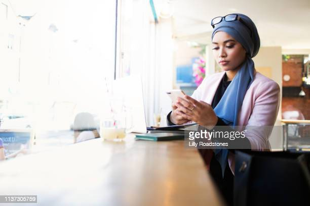 young muslim woman using phone in cafe - looking stock pictures, royalty-free photos & images