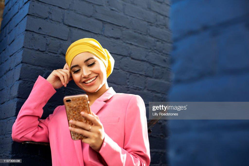Young Muslim woman using phone : Stock Photo