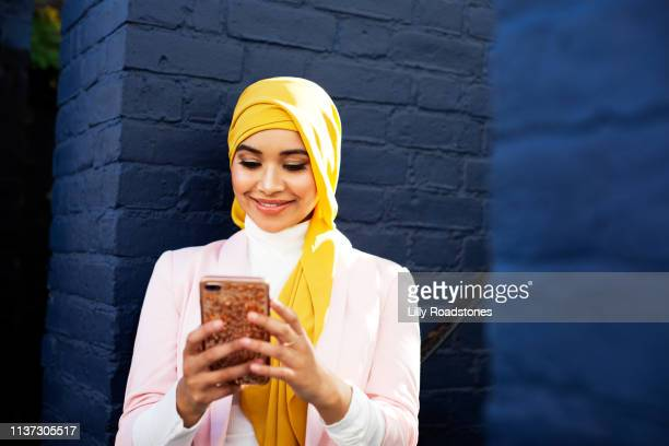 young muslim woman using phone - religious veil stock pictures, royalty-free photos & images