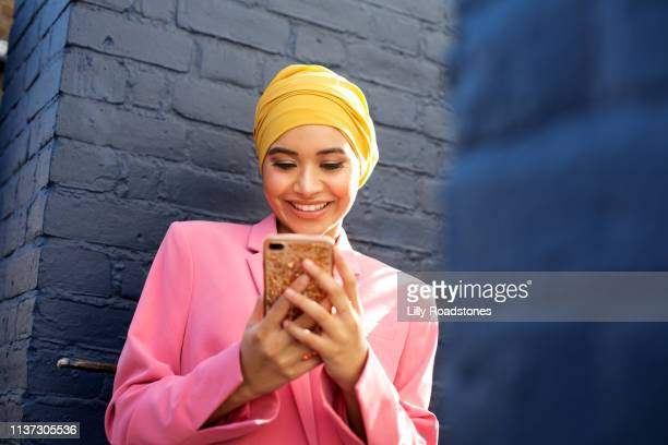 young muslim woman using phone - lifestyles stock pictures, royalty-free photos & images