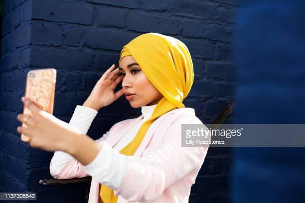 young muslim woman using phone - zurückhaltende kleidung stock-fotos und bilder