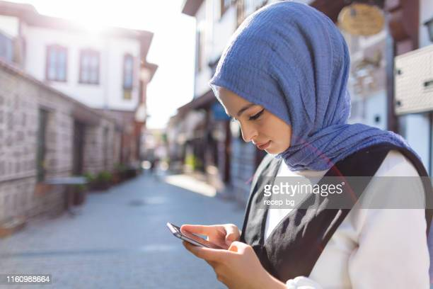 young muslim woman using smart phone in city - beautiful turkish girl stock pictures, royalty-free photos & images
