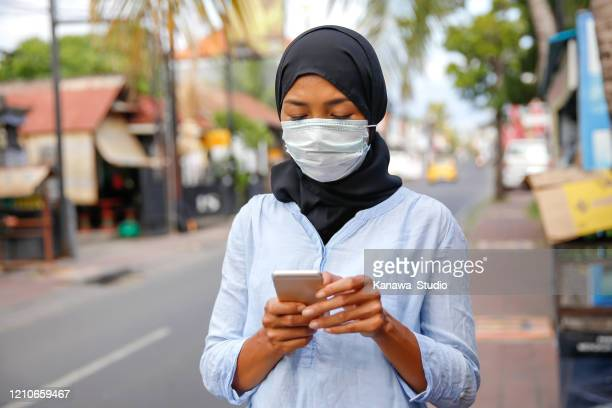 young muslim woman using smartphone on the street - indonesia stock pictures, royalty-free photos & images