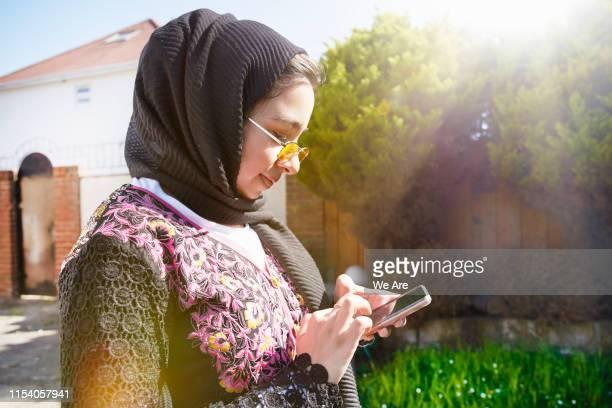 Young muslim woman using smartphone