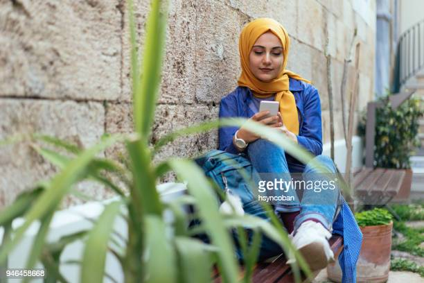young muslim woman using smartphone - religious dress stock photos and pictures