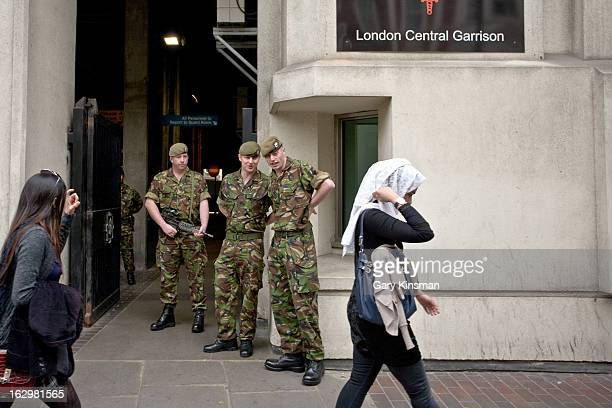 Young Muslim woman walks past some soldiers outside the Central London Garrison, Westminster, Central London, 2011