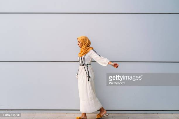 young muslim woman wearing yellow hijab and walking in front of a white wall - scarf stock pictures, royalty-free photos & images