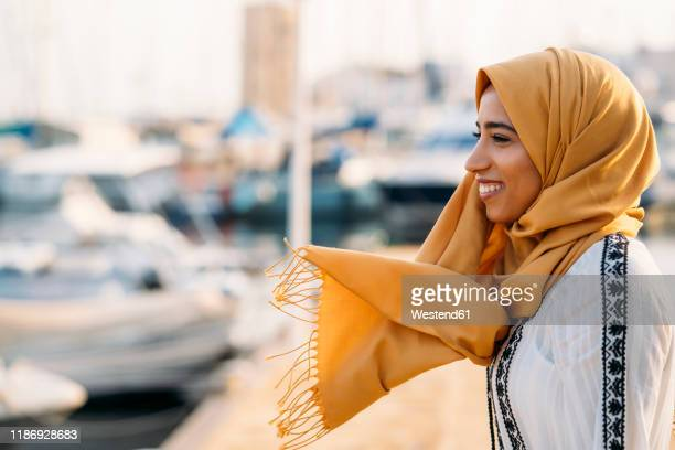 young muslim woman wearing yellow hijab walking at the harbour - north african ethnicity stock pictures, royalty-free photos & images