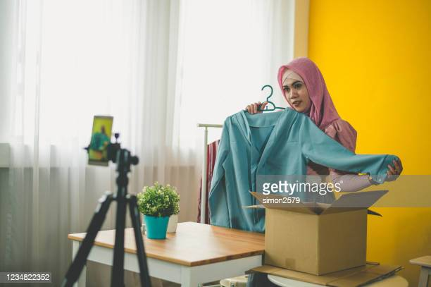 young muslim woman with hijab working live streaming online clothing store at home - live event stock pictures, royalty-free photos & images