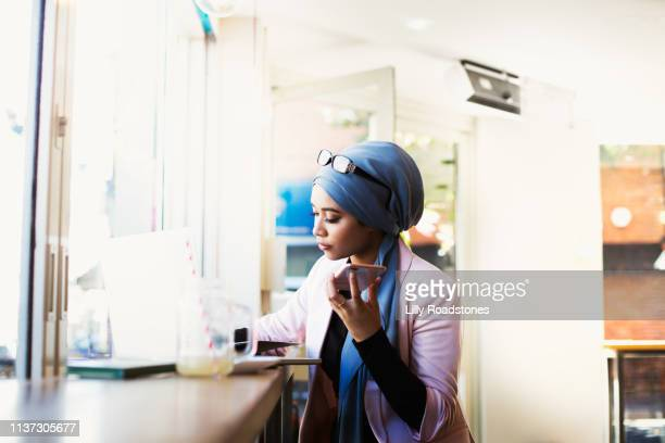 young muslim woman working in cafe - planning stock pictures, royalty-free photos & images