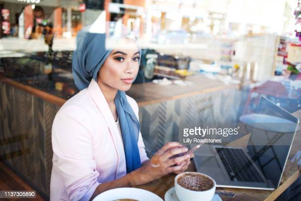 young muslim woman working in cafe - confidence stock pictures, royalty-free photos & images