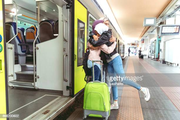 Junge muslimische Frauen am Bahnhof verlassen für eine Reise