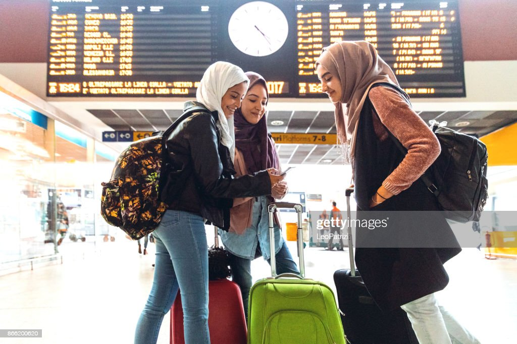 Young muslim women at train station leaving for a journey : Stock Photo