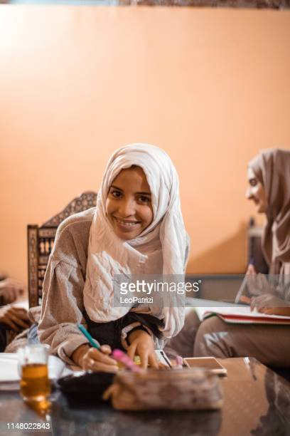 young muslim women cooperating preparing a school exam - moroccan culture stock photos and pictures
