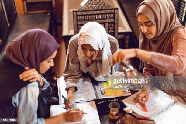 young muslim women cooperating preparing a school exam - moroccan girls stock photos and pictures