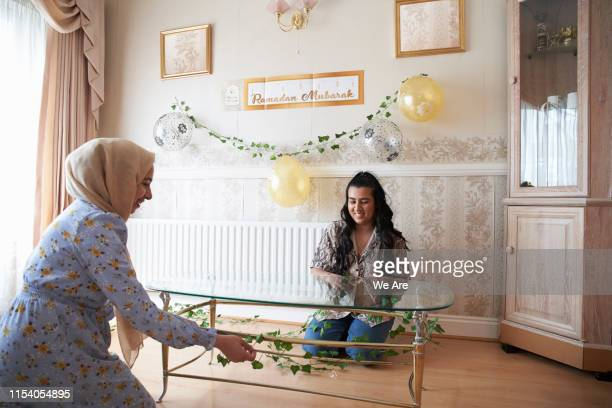 young muslim women decorating home for party - ramadan decoration stock pictures, royalty-free photos & images