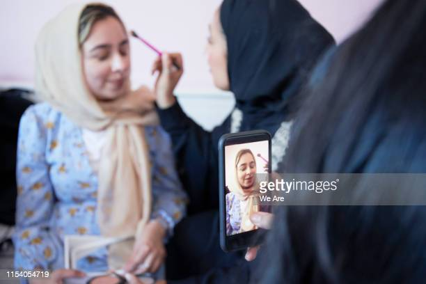 Young muslim women giving friend a make-over in bedroom