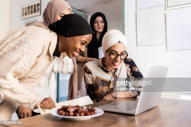young muslim women on video call, with plate of dates - ヒジャブ ストックフォトと画像