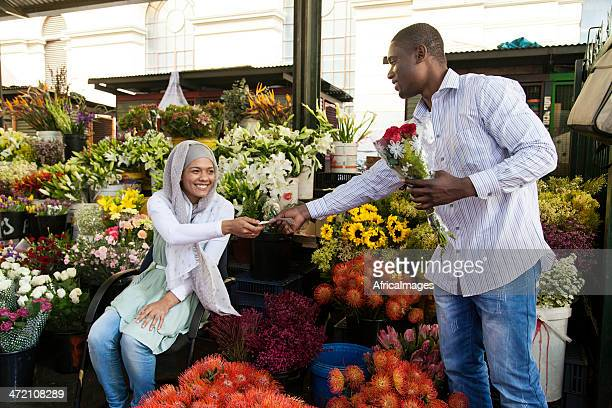 Young muslim women selling flowers to an african male.