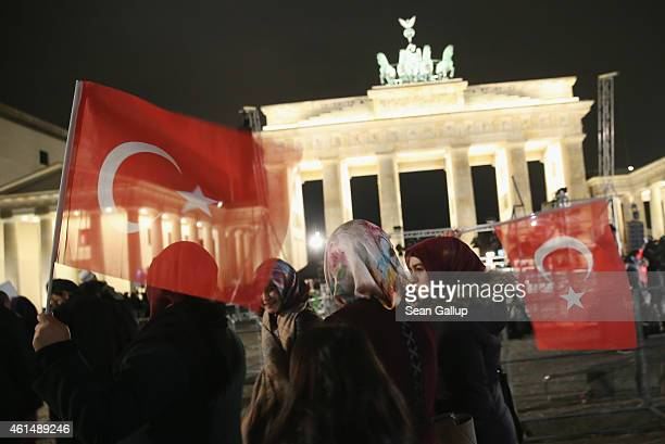 Young Muslim women wearing headscarves and holding Turkish flags walk past the Brandenburg Gate following a vigil organized by Muslim groups to...
