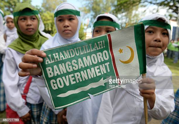 Young Muslims hold a Moro Islamic Liberation Front miniature flag as they gather for a rally in support of the peace agreement with the government in...