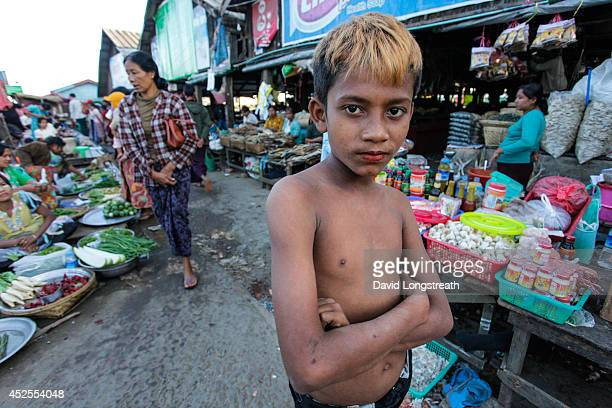 Young Myanmar boy, working as a day laborer, strikes a pose while working at a afternoon market.According to Non Governmental Organizations, child...