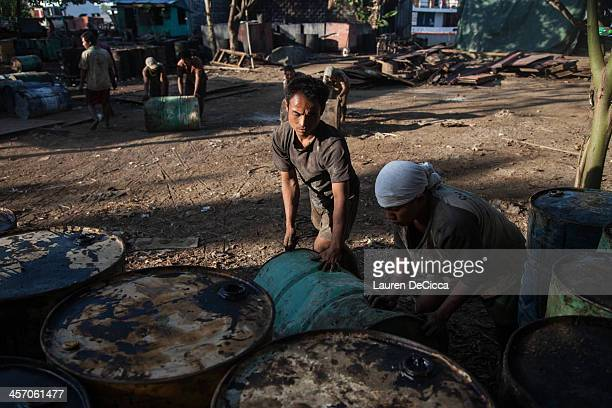 Young Myanmar laborers stack recycled oil drums weighing 240kg on the banks of the Irrawaddy River in the Dala township of Yangon on December 16 2013...