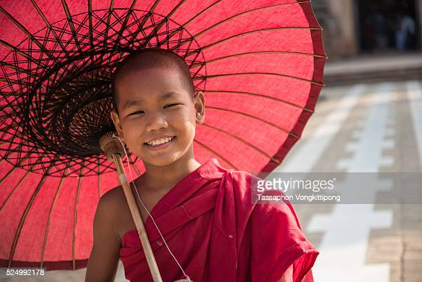 young Myanmar monk smiling holding umbrella