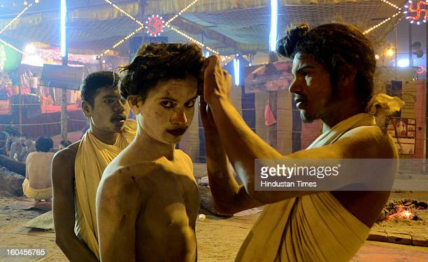 Young Naga busy setting hairs of another before the evening prayer in Bada Udaseen Akhara, in the Kumbh mela area on January 31, 2013 in Allahabad,...