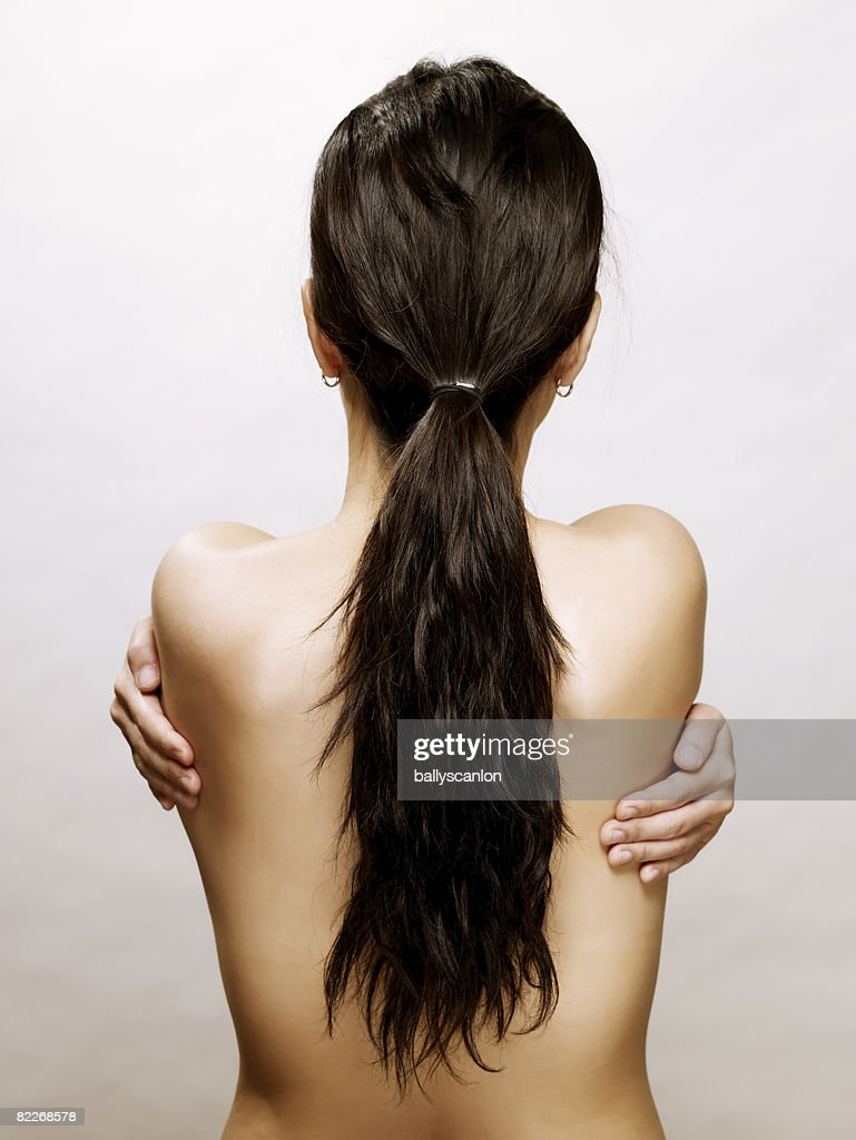 Young naked asian woman holding herself, rear view : Stock Photo