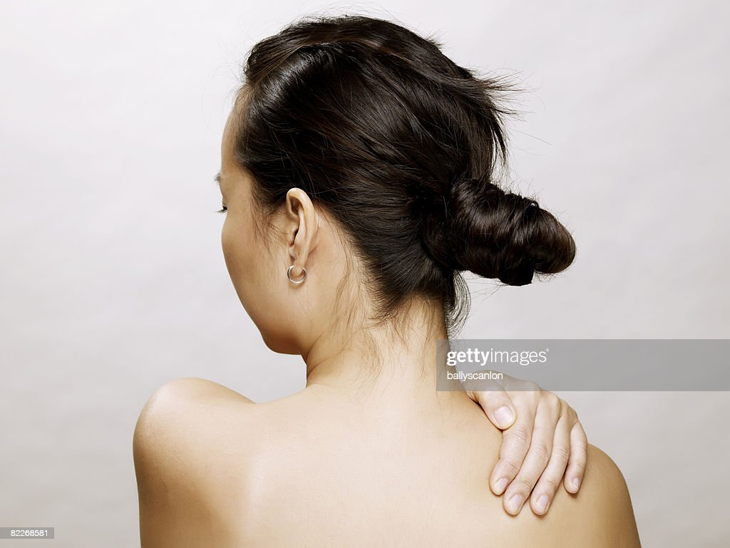 Young naked asian woman with hand on her shoulder : Stock Photo