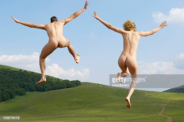 young naked couple running and jumping in mountain field, back view - pareja desnuda fotografías e imágenes de stock