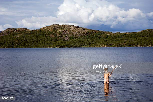 Young naked girl raking the bottom of a lake, Sweden.