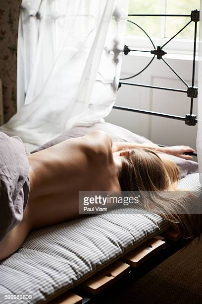 young naked woman asleep in bed.