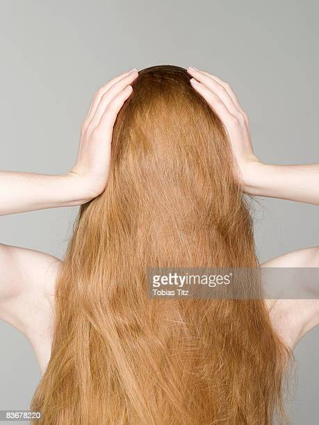 A young naked woman with her hair covering her face and her hands on her head