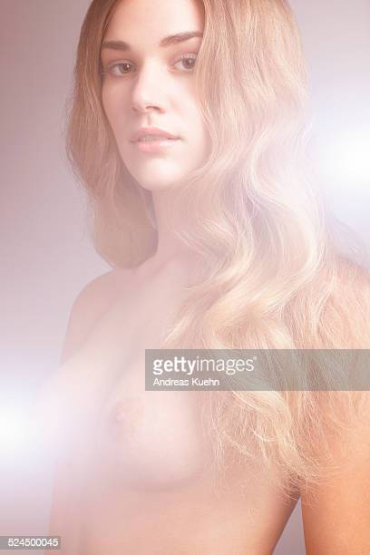 Young naked woman with long, blond hair, portrait.
