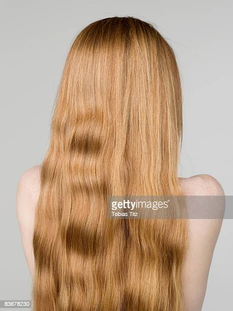 A young naked woman with long hair, rear view