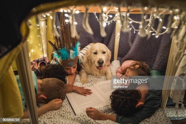 Grupo de niños y niñera joven durmió durante la narración en una tienda de campaña.