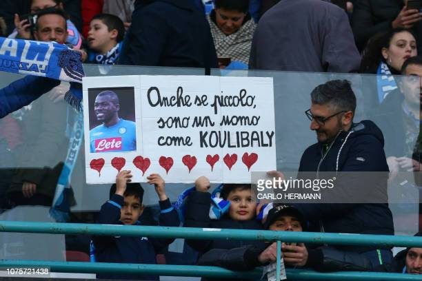 Young Napoli fans hold a portrait of Napoli's Senegalese defender Kalidou Koulibaly reading Although I am small I'm a man like Koulibaly prior to the...