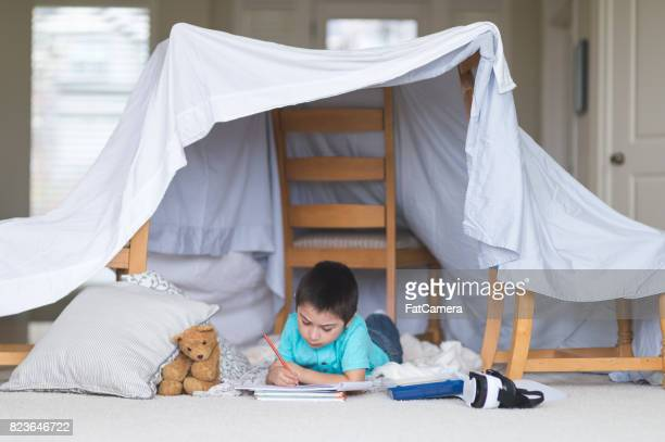Young Native American boy draws in his sketchpad underneath his blanket fort in the living room