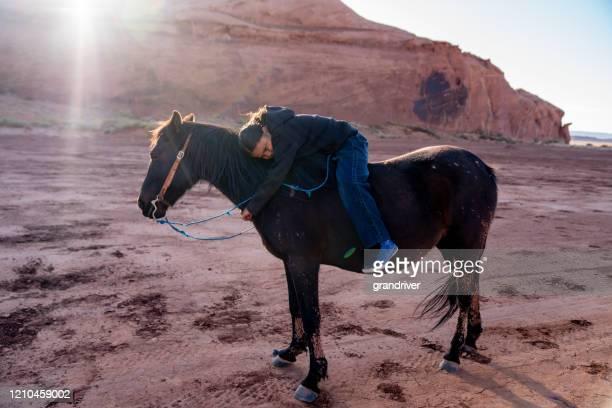 馬の周りに腕を回す若いネイティブアメリカンの少年 - 南西 ストックフォトと画像