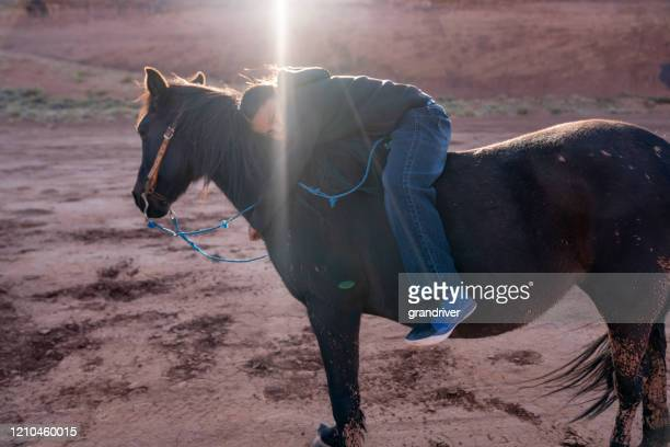 a young native american boy putting his arms around his horse - apache indian stock pictures, royalty-free photos & images